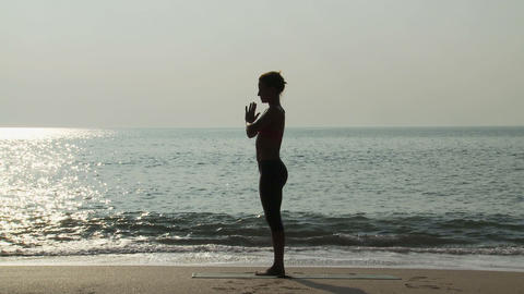 Silhouette of woman by sea in prayer pose Stock Video Footage