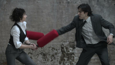 Woman and man fighting with pugil sticks Stock Video Footage
