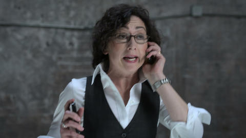 Businesswoman having conversations on two cellphones Stock Video Footage