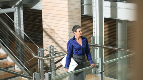 Businesswoman looking at camera and walking up stairs Stock Video Footage