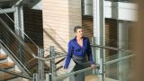 Businesswoman looking at camera and walking up stairs Footage