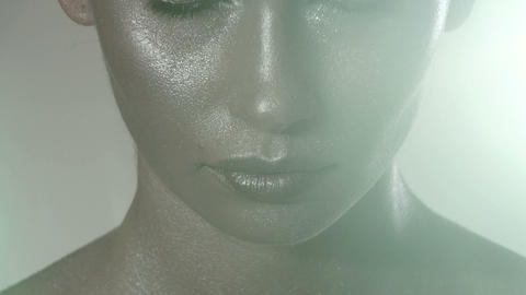 Young woman opening eyes, metallic make up on face Stock Video Footage
