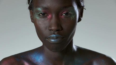 Young woman with metallic make up, looking down and looking at camera Live Action