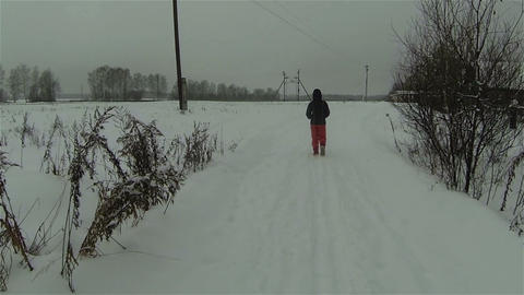 Aerial view of man walking across snowy field by winter road in country side rus Footage