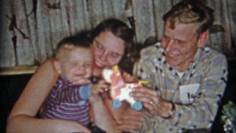 1961: Pocket protector dad and mom playing with new baby at Christmas Footage