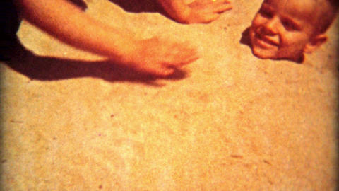 1961: Cute boy buried neck high in beach sand gets out Footage