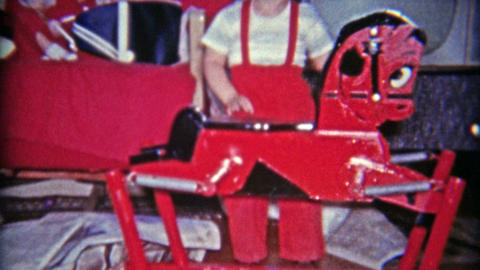 1961: Unwrapping Christmas gift in newspaper of red riding toy horse Footage