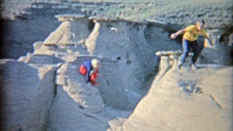 1958: Kids climbing on barren Badlands rock formation getting to the top Footage