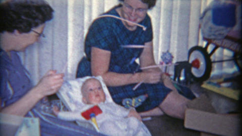 1958: Women mesmerizing baby with butterfly mobile toy Footage