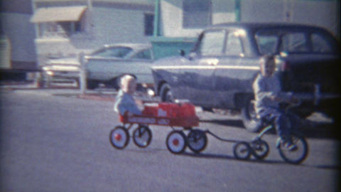 1962: Kid Riding Bike Pulling Wagon Around Mobile Trailer Home Park stock footage