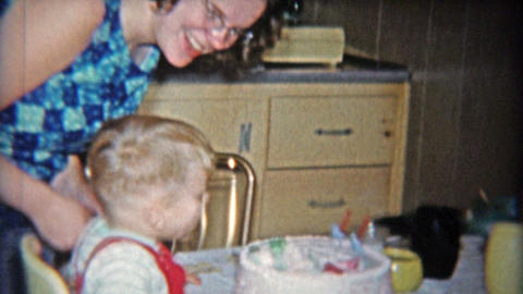 1962: Aunt smokes cigarette while kid blows out 2nd birthday cake candle Footage
