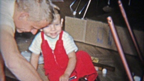 1962: Dad and toddler son building toy rocking horse together from box kit Footage