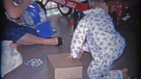 1958: Kid opens Christmas gift of army men in a box Footage
