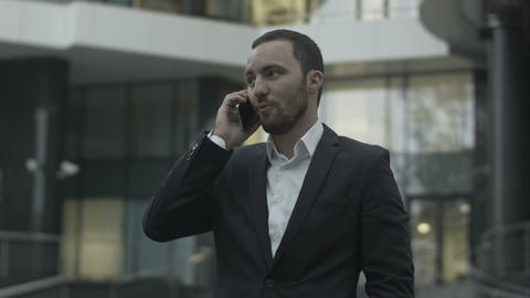 Happy businessman answering call and talk with busness partner standing outside  Footage