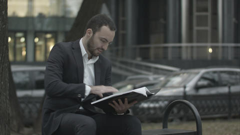 Man in suit reading business plan with interest, sitting on a bench in park and Live Action