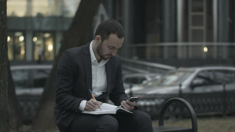 Young Business Man Working With Papers And Phone At Green Park, Waiting For Meet stock footage