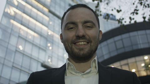 Portrait of young business man on office building background. Caucasian man with Footage
