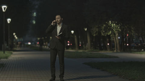 Businessman talking by phone while walking in park and use organizer Footage