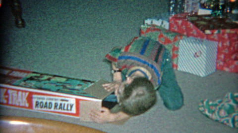 1963: Kid unwrapping road rage electric slot car racer toy for Christmas gift Footage