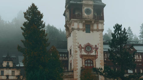 Peles Castle And A Misty Pine Tree Forest In Sinaia, Transylvania, Romania - Clo stock footage
