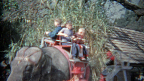 1963: Kids riding on Asian elephant at amusement park ride for privileged childr Footage