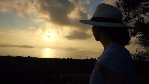 Video Asian Girl Wearing Hat Relaxed Holiday At Golden Sunrise Ocean Beach stock footage