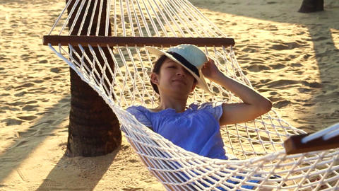 Video Asian woman, girl wearing hat relax on a hammock on the sunny beach with c Footage