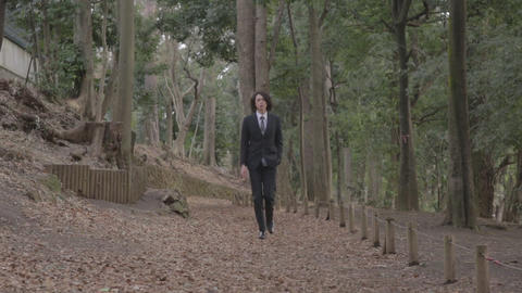 Young man in suit walking in the park Footage