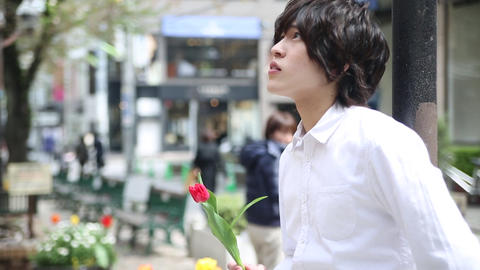 Young man holding a flower Footage