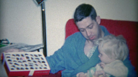 1964: Dad showing child box of chocolates in comfortable morning robe fashion Footage