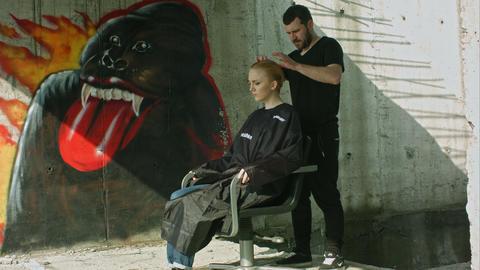Hairdresser making haitcut for a blond girl. Urban Footage