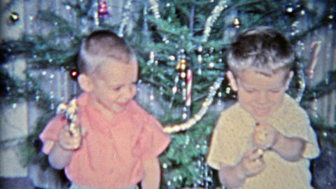 1964: Kids pulling toy guns in front of Christmas tree as you do Footage