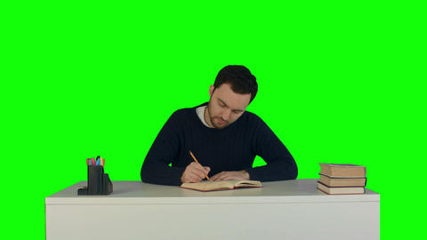 A young man reading a book on laptop on a Green Screen, Chroma Key Footage