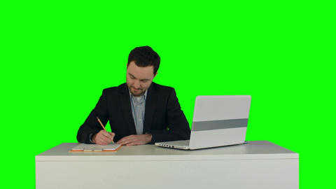 Human hand writing on a paper with laptop on a Green Screen Footage