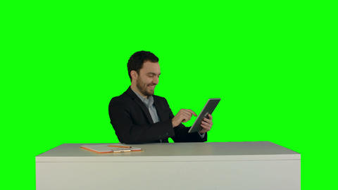 Business man working on digital tablet on his table in his office on a Green Scr Footage