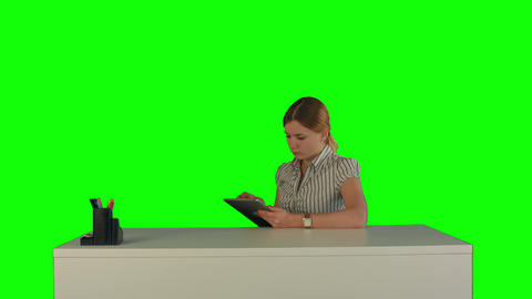 Business woman sitting in her office using a tablet computer on a Green Screen Footage