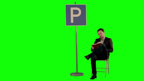 Businessman Reading A Book Near Parking Sign On A Green Screen stock footage