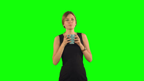 Young beautiful woman holding cup of tea or coffee on a Green Screen Footage