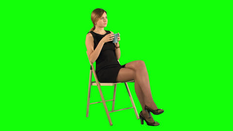 A young attractive woman with a cup of coffee or tea on laptop on a Green Screen Footage