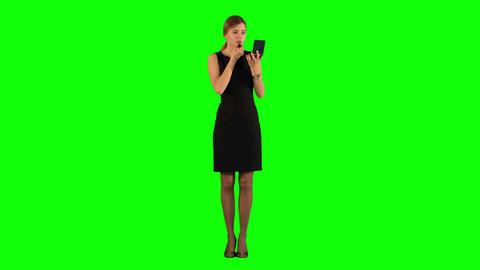 Young adult woman applying lipstick herself on a Green Screen Footage