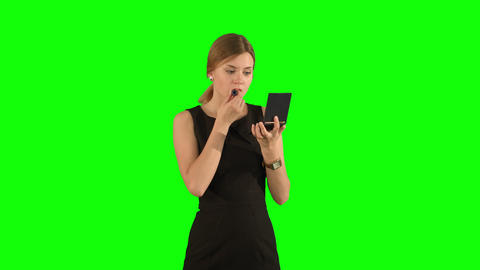 Beautiful woman applying a lipstick on lipson a Green Screen, Chroma Key Footage