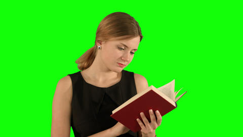 Young beautiful girl reading a book on laptop on a Green Screen, Chroma Key Footage