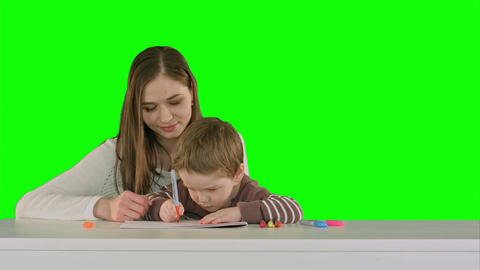 Mom and kid boy painting together on table on a Green Screen Footage