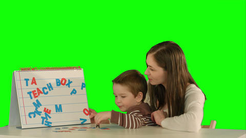 Mother and son make word Mama on the desk on a Green Screen Footage