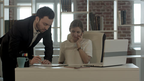 Portrait of a woman making a phone call while her colleague is working in a offi Footage