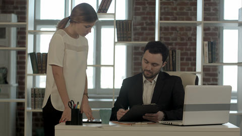 Image of businesswoman pointing document to businessman for signature at the off Footage