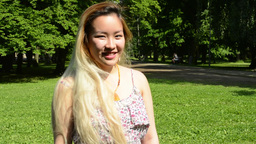 young attractive happy asian woman turns over and smiles in the park - smiles to Footage