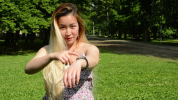 young attractive happy asian woman shows on the watches in the park Footage
