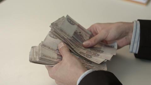 Businessman counts money in hands Footage