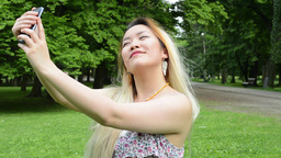 young attractive happy asian woman shoots herself in the park - selfie Footage